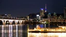 Night scenry of Seoul city with ferry passing by and N South tower in background