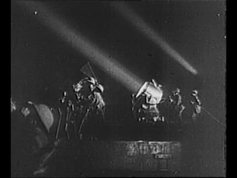 searchlights shine into sky as london air raid wardens look up into night during world war ii / two male air raid wardens and one female stand in... - flugabwehr stock-videos und b-roll-filmmaterial