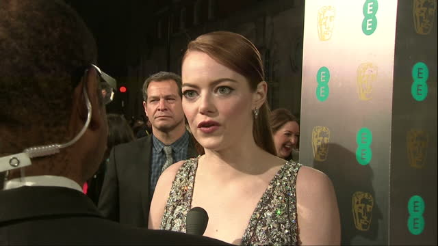 Night shot exterior red carpet shot of Emma Stone La La Land actress talking to reporter at the BAFTA Awards at the Royal Albert Hall on February...