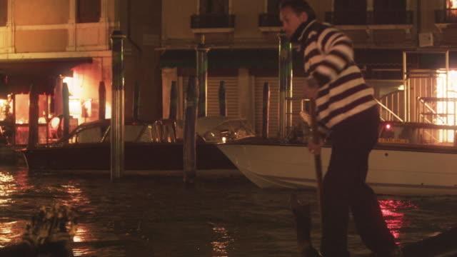 Night shot of gondolier turning boat around