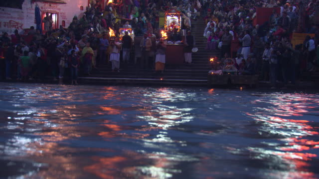 night shot of people gathered on the banks of the ganges in haridwar to perform a hindu ceremony.  - ceremony stock videos & royalty-free footage