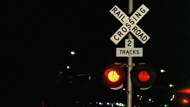 ms night shot of railroad crossing sign, train passing in background, santa barbara, california, usa - level crossing stock videos & royalty-free footage