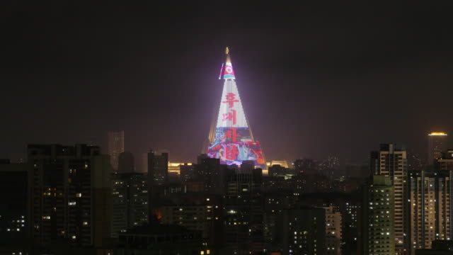 night shot of skyline with ryugyong hotel (pyramid) in pyongyang north korea, drpk. medium shot from above. - spoonfilm stock-videos und b-roll-filmmaterial