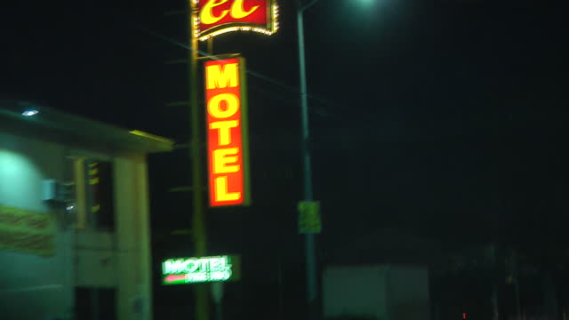 night shots from a car driving around los angeles, passing closed businesses and a motel with an illuminated sign, approaching emergency or recovery... - soft focus stock videos & royalty-free footage