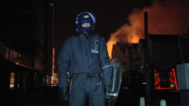 night shots of a police officer wearing riot gear patrolling the cordoned area and orange flames from a fire in the background on august 9 2011 in... - 機動隊点の映像素材/bロール