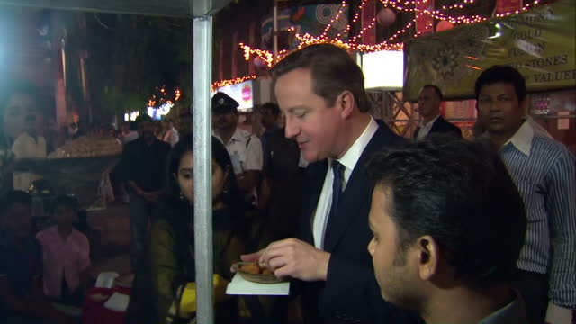 vidéos et rushes de night shots of british prime minister david cameron trying some street food and speaking to stallholders during a visit to a kolkata market david... - calcutta