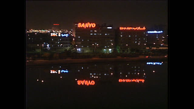 night shots of business signs on buildings lit up at night, including sanyo on december 1, 1990 in jeddah, saudi arabia. - jiddah点の映像素材/bロール