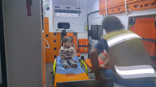 Night shots of children being put into ambulances including Syrian boy Omran Daqneesh looking dazed after strike on August 18 2016 in Aleppo Syria