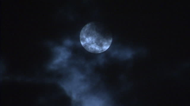 night shots of clouds or smoke passing over the face of the full moon giving it an eerie appearance >> on november 04 2017 in poynton england - cloud sky stock videos & royalty-free footage
