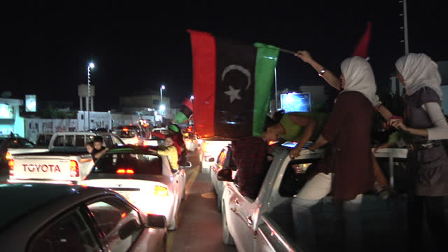 stockvideo's en b-roll-footage met night shots of fighters civilians celebrating their freedom waving flags after the death of colonel gaddaffi on october 25 2011 in tripoli libya - libië