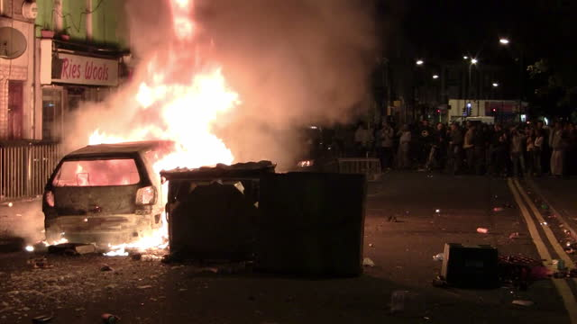 vidéos et rushes de night shots of flames from a car set alight by rioters, rioters breaking into clarence convenience store & looting, taking bottles of drinks on... - hackney