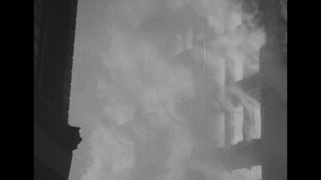 vs night shots of flames shooting out of windows of destroyed gutted buildings during the london blitz heavy smoke / ls down dark street with flames... - the blitz stock videos and b-roll footage