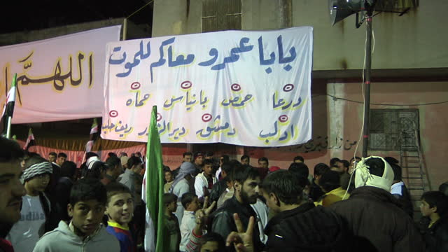 night shots of free syrian army organised protests with protesters holding posters flags of syris and banners protesting against president assad's... - syrien stock-videos und b-roll-filmmaterial