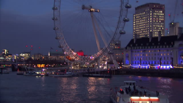 night shots of iconic buildings lit up including london eye a tourist boat on the thames river savoy place new scotland yard and embankment station... - ニュースコットランドヤード点の映像素材/bロール