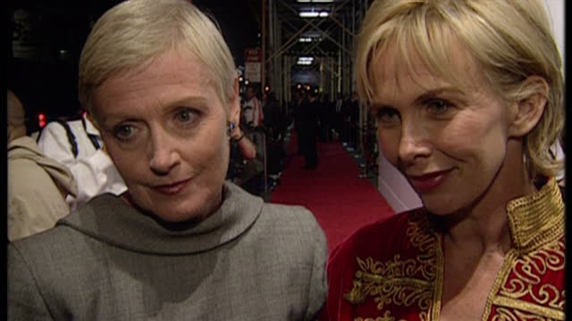 Night shots of Liz Tilberis and Trudie Styler posing on the red carpet and giving an interview about British designers in America at a fundraising...