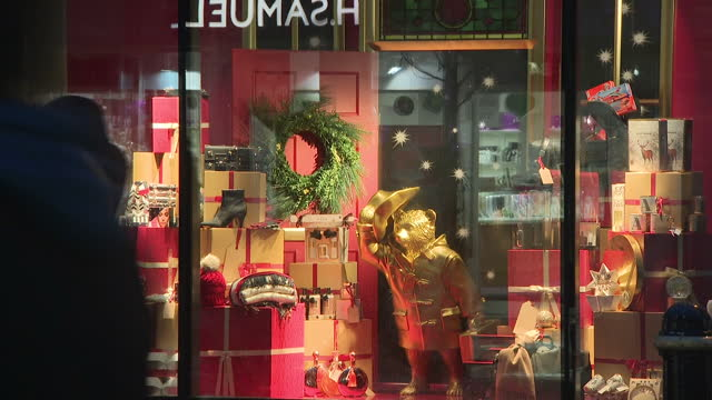 vídeos de stock e filmes b-roll de night shots of pedestrians passing the entrance of a marks spencer store and views of christmas themed window displays of winter clothing and gifts... - marks and spencer