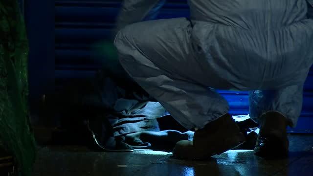 vidéos et rushes de night shots of police forensics officer at stabbing crime scene - crime