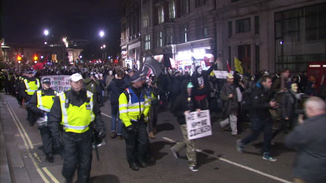 night shots of police moving into position as masked protesters set off from trafalgar square and march along streets wearing guy fawkes masks and... - anonymous stock videos and b-roll footage