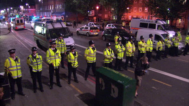 vidéos et rushes de night shots of police officers in a line formation blocking a road with police vans & a police helicopter nearby, at the scene of rioting in hackney... - hackney