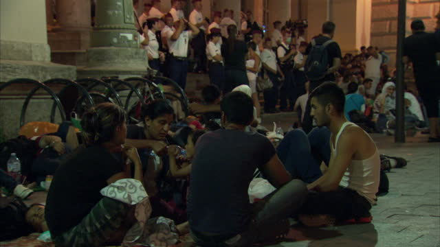 night shots of refugees sat outside keleti station waiting to be transported to germany on september 9 2015 in budapest hungary - flüchtlingslager stock-videos und b-roll-filmmaterial