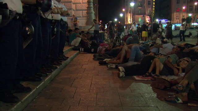 night shots of refugees sleeping outside keleti station and police officers stood nearby on september 9, 2015 in budapest, hungary. - budapest stock-videos und b-roll-filmmaterial