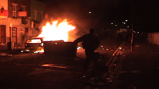 vidéos et rushes de night shots of rioters watching flames rising from a car on fire in the street during the london riots in hackney on august 9, 2011 in london,... - hackney