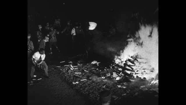 Night shots students and Nazis walk past bonfire and throw books into fire swastika can be seen on a couple of armbands / German propaganda minister...