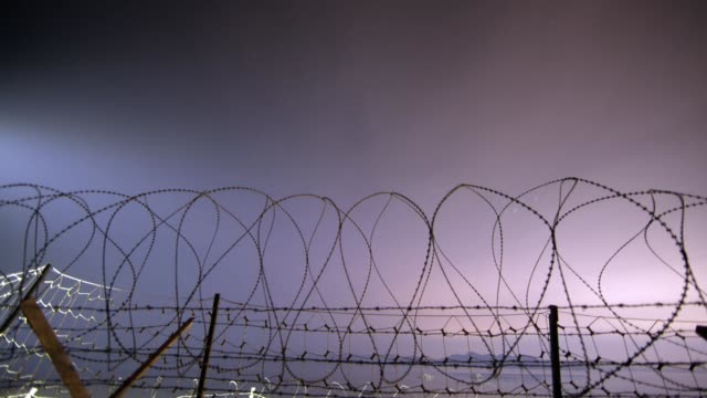 night sky of barbed wire fence in demilitarized zone / ganghwado island, incheon, south korea - fence stock videos & royalty-free footage