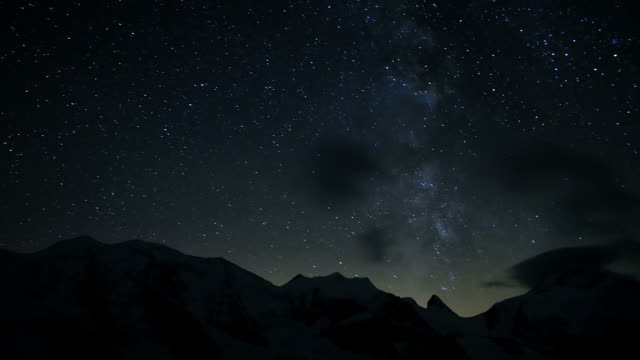 night sky over mountains and glacier, timelapse into new day