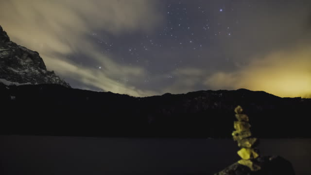 vídeos y material grabado en eventos de stock de t/l night sky timelapse at lake eibsee with a cairn in the foreground - montón de piedras