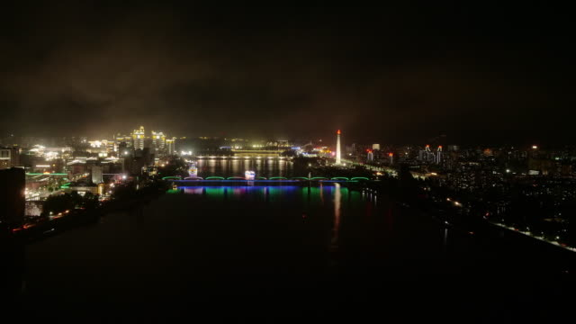 night skyline of pyongyang north korea, drpk. wide shot from above sunset with riverboat cruising on taedong river. - spoonfilm stock-videos und b-roll-filmmaterial