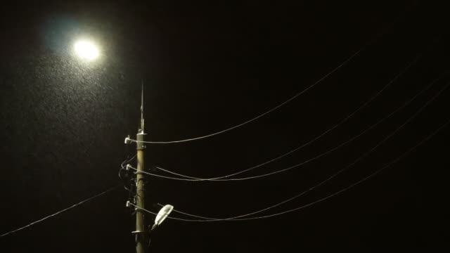 night snowfall on the background of a street lamp - linea telefonica video stock e b–roll