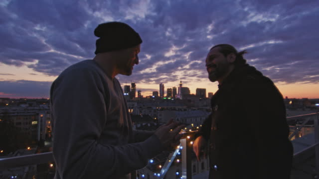 night talks on the rooftop. city after sunset - guardare il paesaggio video stock e b–roll