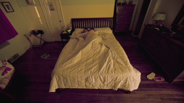 T/L WS HA Night till day view of woman sleeping in bed / New York City, New York State, USA