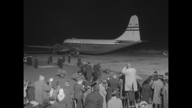 tilt numerous movie cameras / empty space flanked by crowds of people / boac airplane taxis into the darkness as queen elizabeth ii departs on her... - british empire stock videos & royalty-free footage