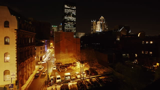 night time lapse montreal with notre dame in front of aldred building, wide shot - vieux montréal stock-videos und b-roll-filmmaterial