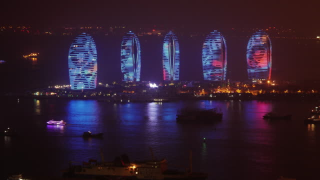night time lapse of futuristic  illuminated skyscrapers on phoenix island in sanya, hainan province, china. medium wide view from above - spoonfilm stock-videos und b-roll-filmmaterial