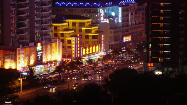night time lapse of traffic on a shopping street in sanya, hainan province, china. shot from above - spoonfilm stock-videos und b-roll-filmmaterial