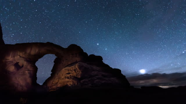 A night time lapse of Turret Arch in Arches National Park (near Moab, Utah) with occasional shooting stars and a field of stars that becomes obscured by low, heavy clouds.