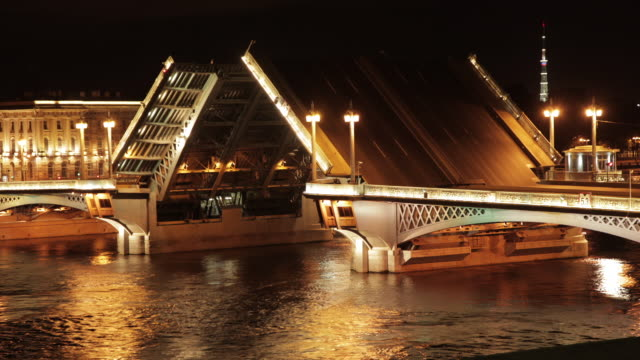 Night time lapse shot of a bascule bridge opening to allow a boat to travel along the Neva River in St Petersburg.