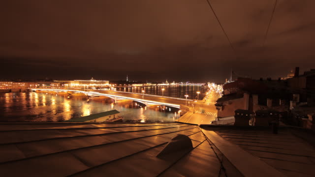 Night time lapse shot of traffic travelling over a bascule bridge in St Peterburg.
