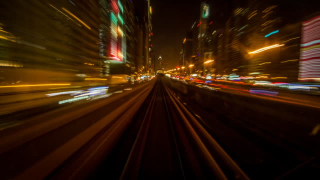 night time lapse shot travelling along a railway line in the city of dubai. - vereinigte arabische emirate stock-videos und b-roll-filmmaterial