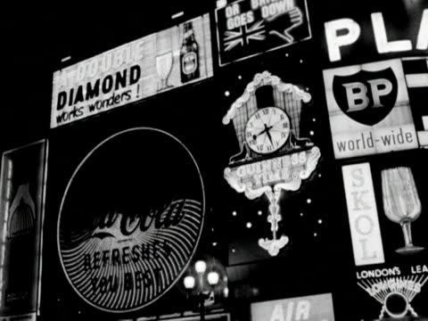 night time shot of the neon advertising hoardings at piccadilly circus; 1961. - commercial sign stock videos & royalty-free footage