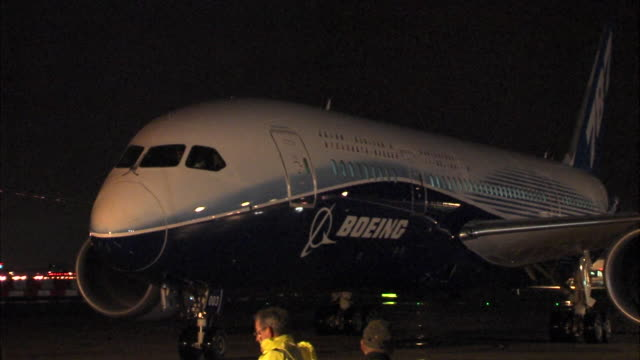 vídeos de stock, filmes e b-roll de night time shots of boeing 787 'dreamliner' taxiing at heathrow as part of a promotional tour. pulls up to a halt on tarmac in front of camera which... - boeing 787