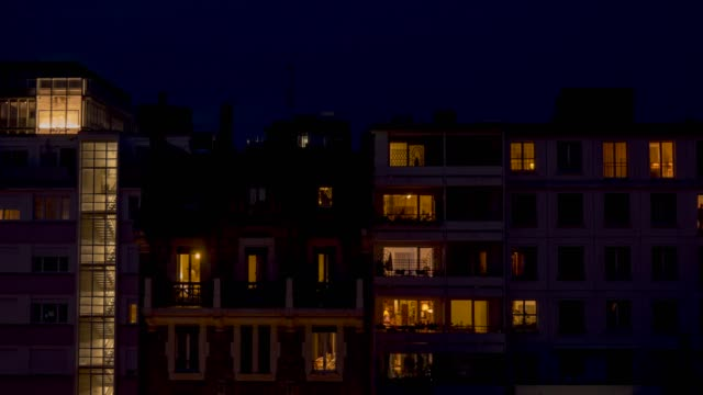 night time time lapse of apartment buildings and their residents. - standbildaufnahme stock-videos und b-roll-filmmaterial
