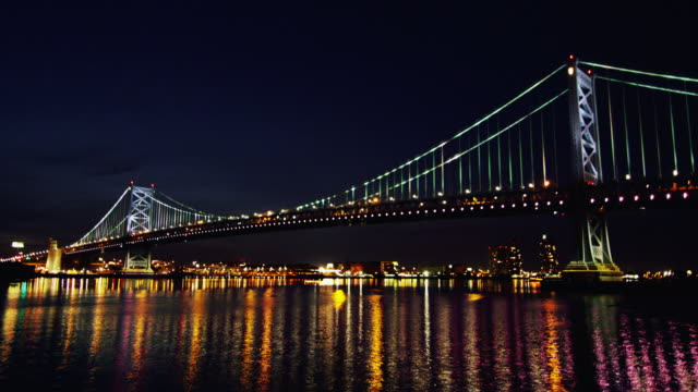 vídeos de stock e filmes b-roll de night time, time lapse of philadelphia cityscape, with delaware river and ben franklin bridge in foreground. - ponte ben franklin