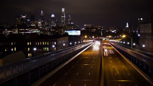 vídeos de stock e filmes b-roll de night time time lapse philadelphia cityscape with the traffic crossing the ben franklin bridge in the foreground. - ponte ben franklin