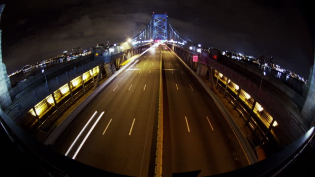 Night time, time lapse, wide angle of Philadelphia cityscape, overhead shot traffic crosses the Ben Franklin Bridge.
