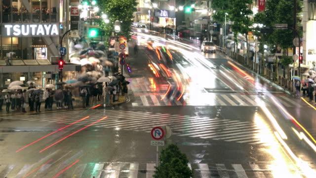 vídeos de stock, filmes e b-roll de tempo da noite-lapso arial vista do cruzamento de shibuya em tokyo, japão - caos