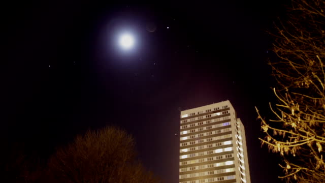 night time timelapse of the moon and stars with a city housing block or project housing